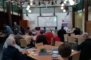 zaal met mensen die kijken naar video in het Stigma Café