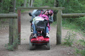 vrouw in scootmobiel moet bukken om in een bos onder een houten balk door te kunnen rijden