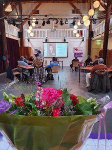Zaal met mensen die luisteren naar een spreker met op de voorgrond bloemen